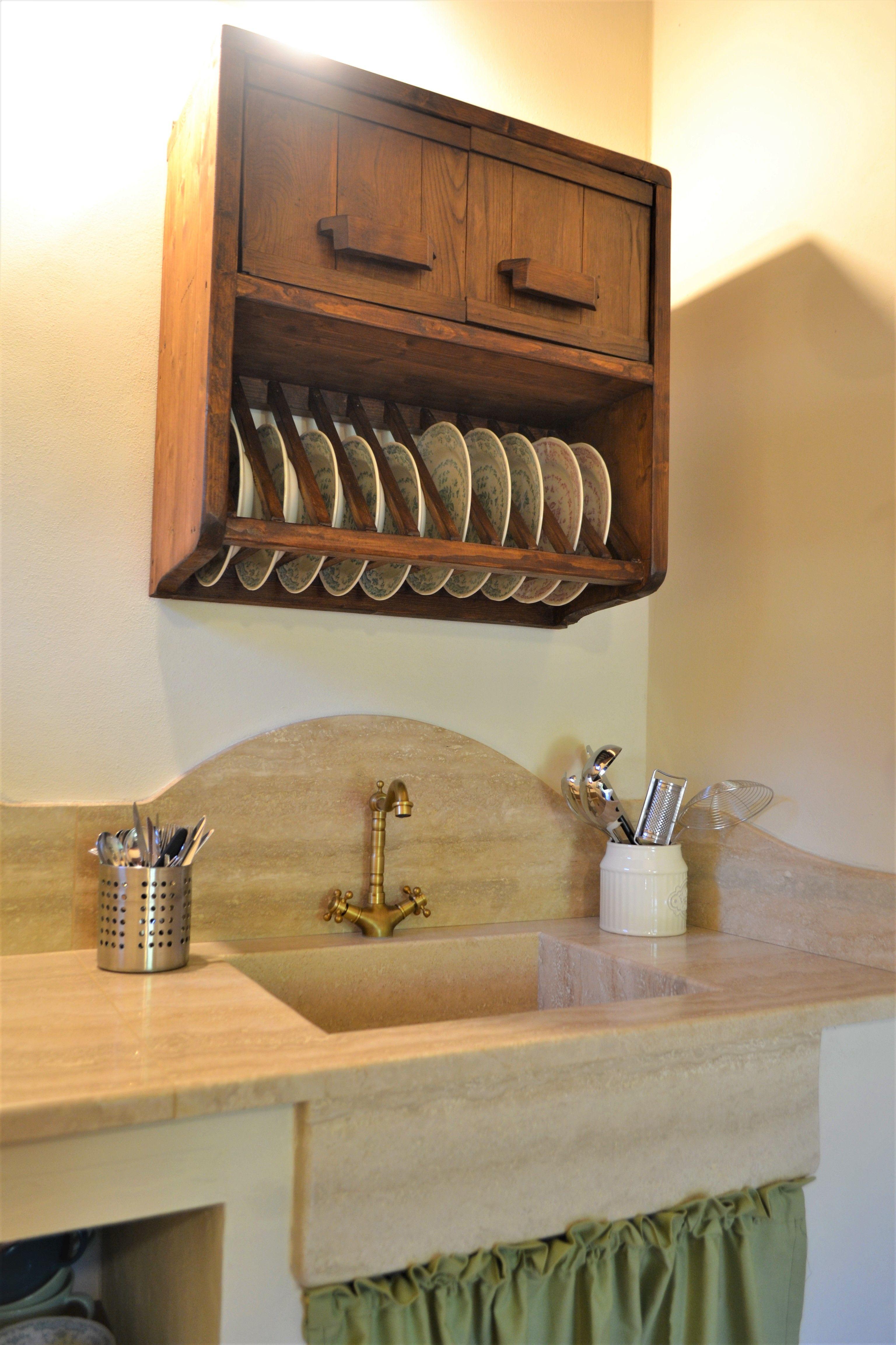 Cucina in stile rustico con piano di lavoro in travertino e mobili in legno di realizzazione artigianale.