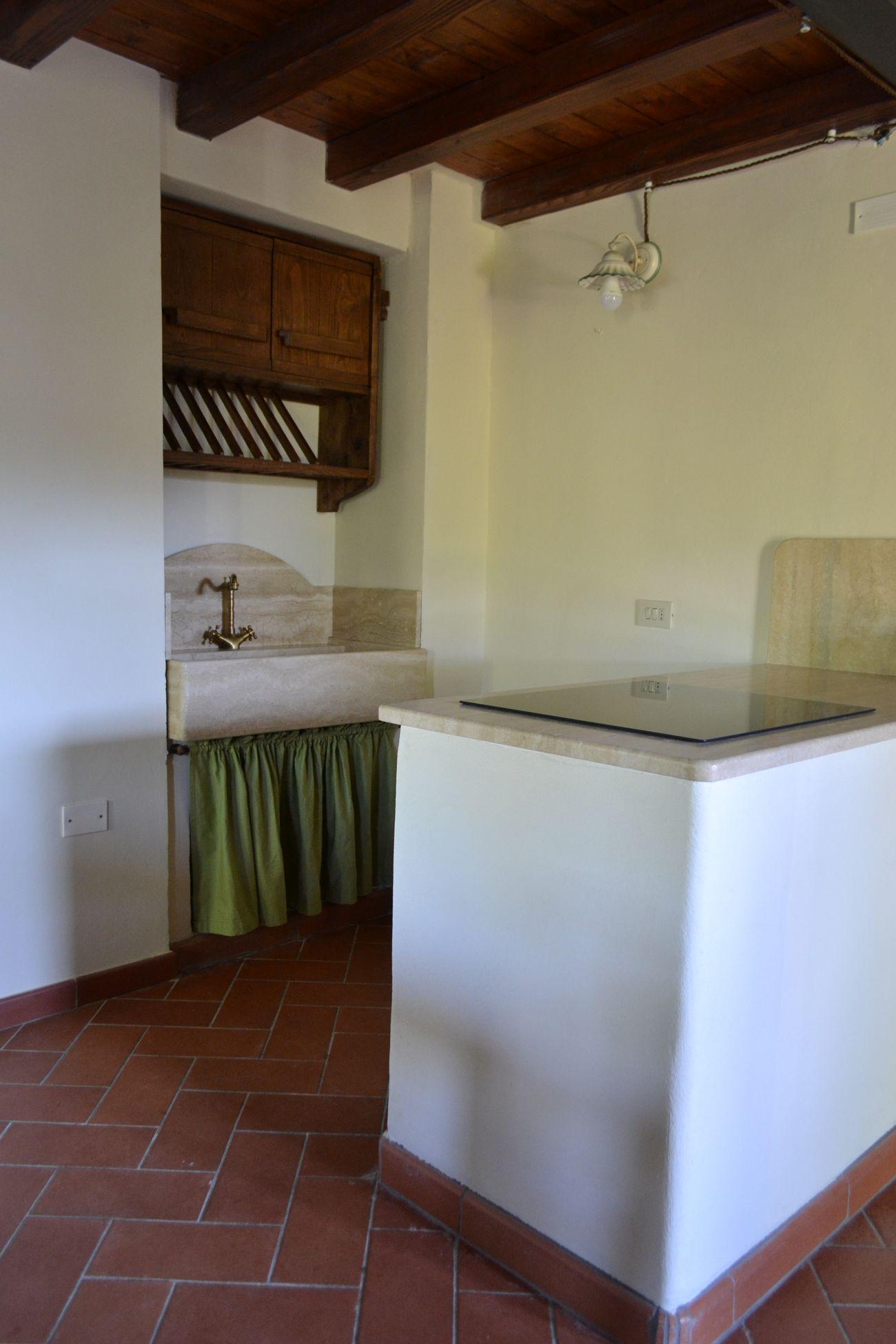 Cucina in stile rustico, piano di lavoro in travertino, fornelli ad induzione, mobili in legno di realizzazione artigianale.